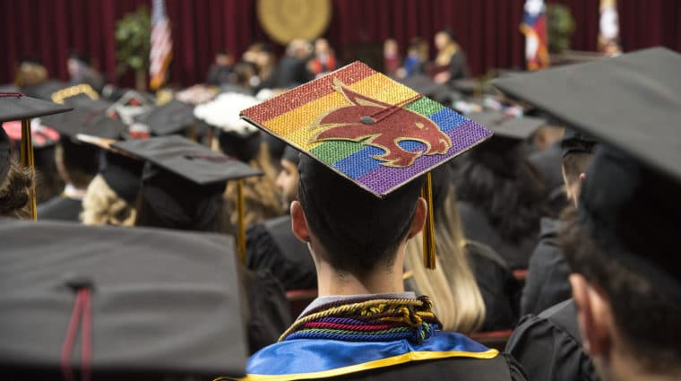 a graduate whose cap features a rainbow and a supercat